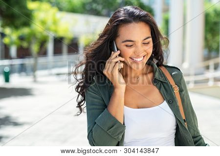 Cheerful young woman looking down on street while talking over smartphone. Smiling girl walking on street and talking on phone. Smiling businesswoman having pleasant conversation on mobile phone.