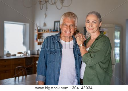 Senior man and woman standing in new house looking at camera. Portrait of old couple relaxing at home. Elderly husband and mature wife looking at camera.