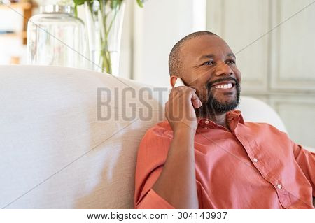 Cheerful mature man talking on smartphone. Black man at home relaxing while talking on cellphone. Happy african american guy sitting on couch in conversation through mobile phone with copy space.