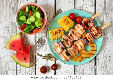 Summer Bbq Or Picnic Food Concept. Salad, Grilled Kabobs, Corn And Fruit. Top View Table Scene Over