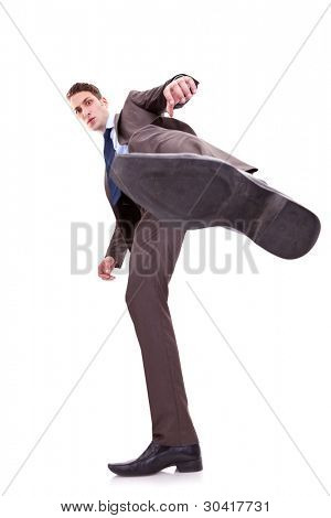 young business man kicking something on white background. wide angle shot, view from bellow
