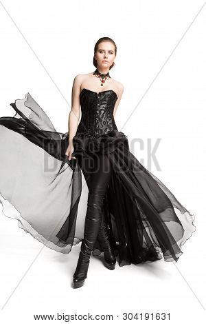 Fashion Model Black Corset Dress, Leather Pants, Beautiful Woman In Gothic Gown Isolated Over White