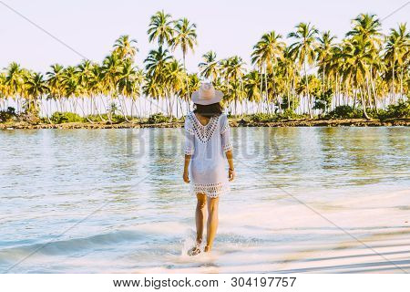 Traveler Girl Walking In White Dress On A Tropical Beach. Young Girl Traveler Walking In Nature. Tra