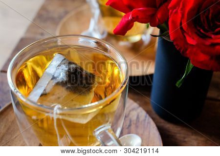 In Coffee Shop, The Hot Lavender Tea In Glass Serve With Wooden Saucer On The Table With Rose Flower