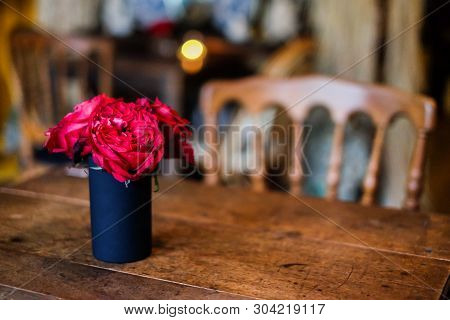 In Coffee Shop (cafe), The Red Rose Flower In Black Vase On The Table For Background Or Texture - Vi