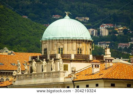 Carciotti Palace, Trieste, Italy. The Dome And Part Of The Facade And Hills In Background