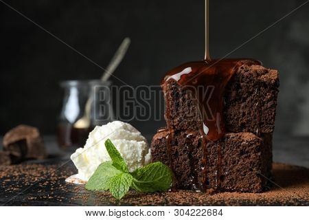 Pouring Sauce Onto Fresh Brownies Served With Ice-cream On Slate Plate, Space For Text. Delicious Ch