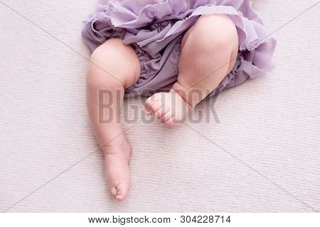 Mother Holds The Feet Of The Newborn Baby With Her Hands, Fingers On The Foot, Maternal Care, Love A
