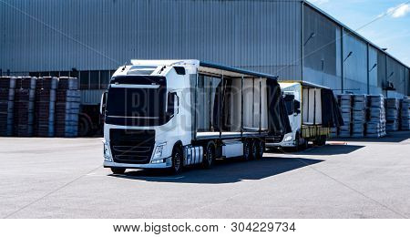 Cargo Truck At Warehouse Building . The Truck With The Trailer On Loading . The Truck With The Semi-