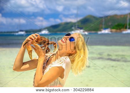 Tourism in Seychelles, Africa, Indian Ocean. Happy tourist woman holding an Ocypode Ceratophthalmus also called Ghost Crab with one claw being larger than the other. Curieuse Island Nature Reserve. poster