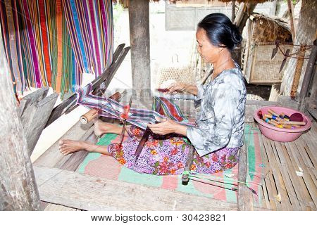 LOMBOK, INDONESIA - FEBRUARY 14 - An elderly weave songket (traditional colorful fabric) using the classic loom on February 14,2012 in Sade,Lombok. Sade village is famous for their beautiful cloth
