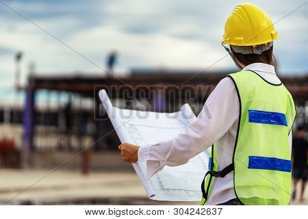Woman Engineers Wear Safety Hats And Hold Blueprints In Their Hands.