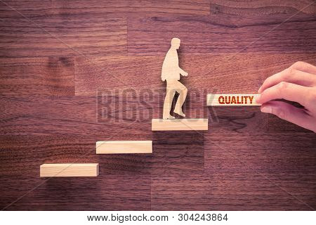 Coach Motivate To Quality Improvement. Hand With The Last Peace Of Stair And Person Made From Wood A
