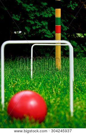 Close Up Of Red Croquet Ball With Wickets In Background