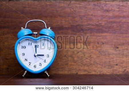 Heart Shaped Alarm Clock On Wooden Background. Time Is Three O Clock