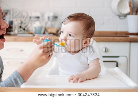 Charming Little Baby Boy 6-8 Months Eating First Food Pumpkin From Spoon With Mom At The Home