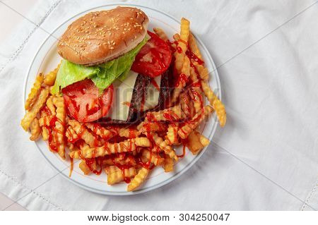Burger And French Fries.the Concept Of Junk Food. Top View. White Background. Copy Space For Your Te
