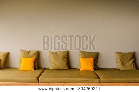 A backless seat sofa with five square khaki pillows and two bright yellow pillows. Copy space poster