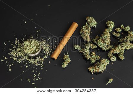 Close Up Of Addict Lighting Up Marijuana Joint With Lighter. Man Preparing And Rolling Marijuana Can