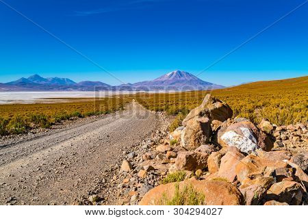 View Of Salar De Uyuni With The Dormant Volcano And A Dirty Road In Bolivia