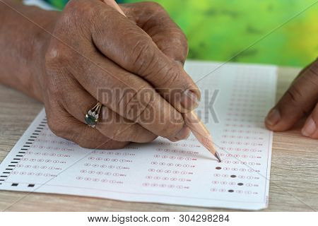 Close-up Image Of Elderly Asian Woman Hands Doing Exams By Using Pencil Selected Multiple Choice On