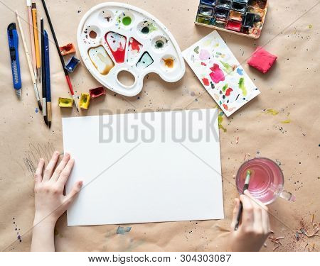 Creative person working with professional artistic worktools on brown sheet of paper, mock-up