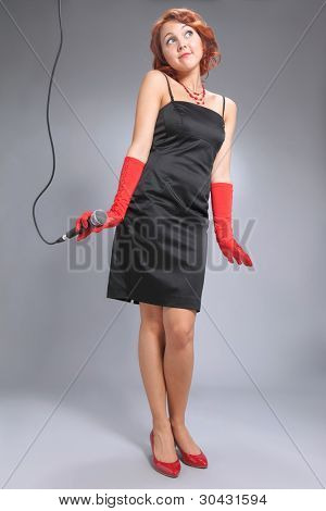 Young woman with microphone standing on grey background in black dress with red accessories.