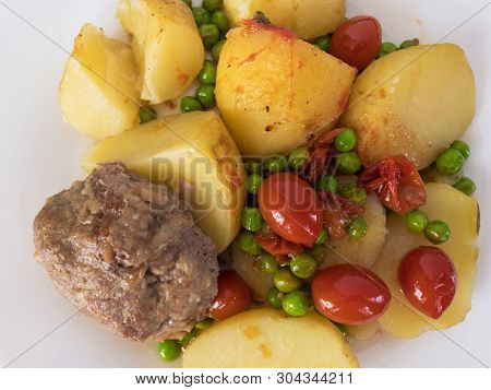 Top View On A Plate With Boiled Potato, Rissole, Cherry Tomatoes Roasted With Green Peas
