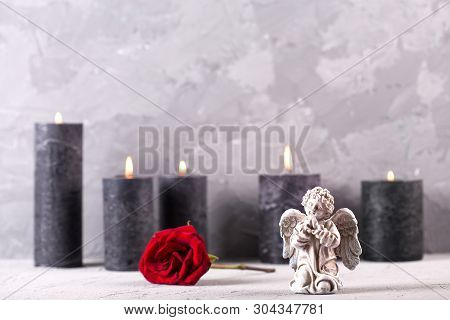 Mourning Concept. Little Angel, Bright Red Rose Flower And Burning Candles On Grey Textured Backgrou