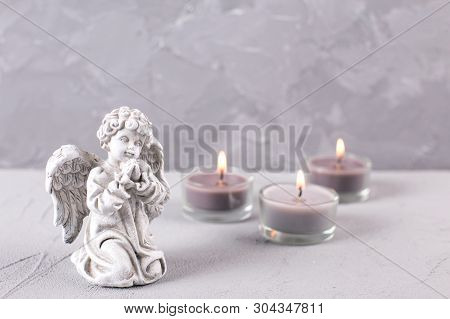 Mourning Concept. Little Angel And Burning Candles On Grey Textured Background. Card For Mourning, D
