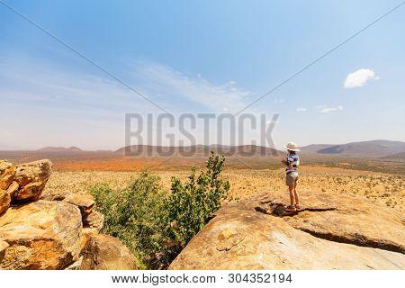 Young girl on African safari vacation enjoying view over Samburu Kenya