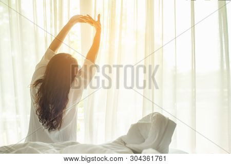 Asian Women Waking Up Stretching In Bed At Home, Morning And Sunny Day.  Lifestyle Concept