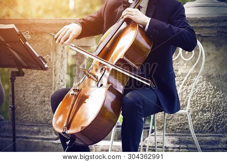 Musician In A Black Suit Sitting On A White Elegant Chair On The Terrace In The Park And Playing Cla