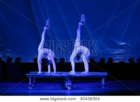 SHANGHAI, CHINA - NOVEMBER 28: A pair of gymnasts from the world famous Shanghai acrobats balance crystal chandeliers for tourist on stage on November 28, 2011 in Shanghai, China.