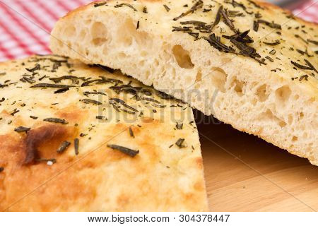 A Loaf Of Homemade Focaccia Bread A Loaf Of Homemade Focaccia Bread On A Wooden Bread Board