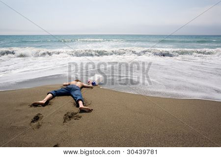 The young man lays at the sea. In a hand the empty canister for fresh water.