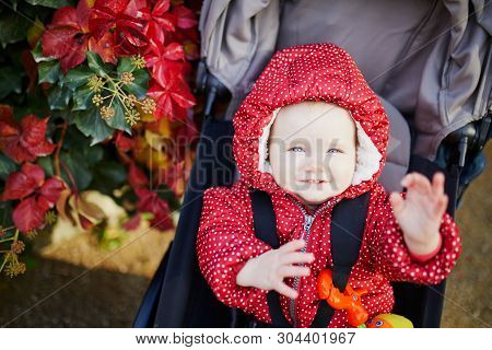 Adorable Little Girl In Bright Stylish Clothes Sitting In Pushchair Outdoors On A Fall Day. Autumn W