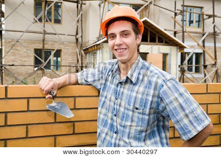 The builder erects a wall from a brick.