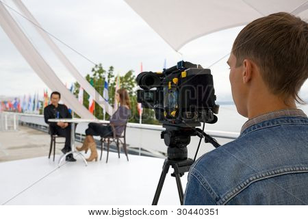 The television operator on a working platform.The reporting from the international festival. poster