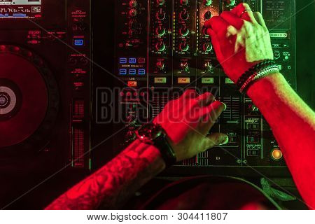 Close Up Of Dj Hands Controlling Music Table In A Night Club.