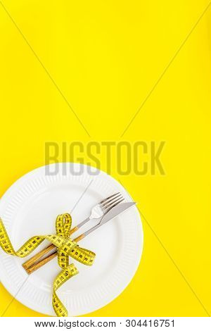 Diet Concept With Plate, Flatware And Measuring Tape For Weight Loss On Yellow Background Top View M