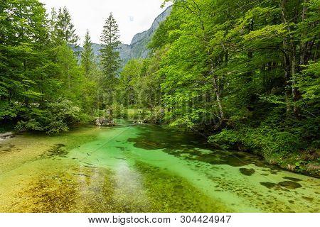 Colorful Spring Panorama Of Sava Bohinjka River At The Bohinj Lake Village Ukanc. Picturesque Moning