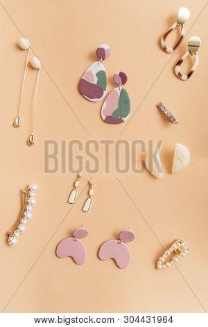 Gold Modern Stylish Earrings On A Beige Background. Different Earrings On A Plain Background. Fashio