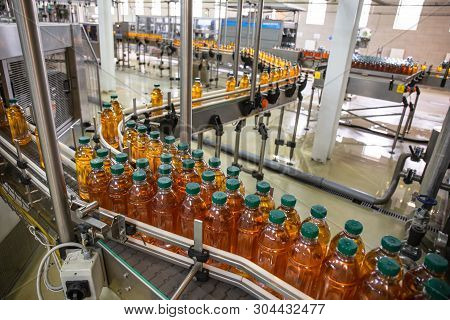 Plastic Bottles With Juice On Automated Conveyor Line Or Belt In Modern Beverage Plant Or Factory Pr