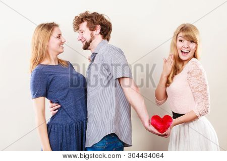 Betrayal And Infidelity Concept. Handsome Boy With Two Attractive Blondie Girls. Man Cheating Women