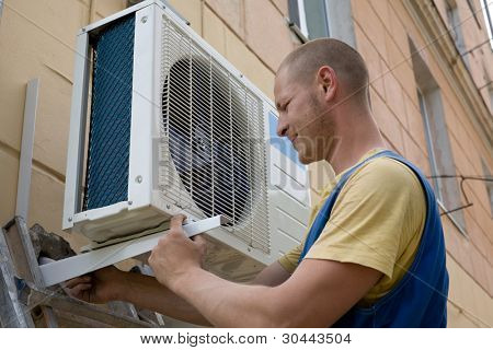 Young setup man installs the new air conditioner for office.
