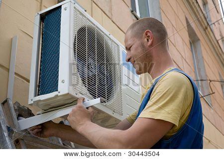 Jóvenes configuración hombre instala el nuevo acondicionador de aire para la oficina.