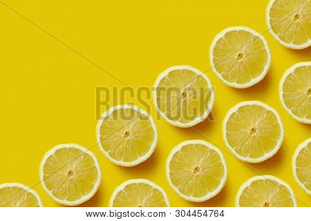 Fresh sliced lemon on yellow background. Creative pattern made of lemon.