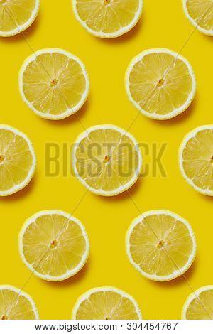 Fresh sliced lemon on yellow background, infinite pattern. Seamless background of fresh lemon slices.