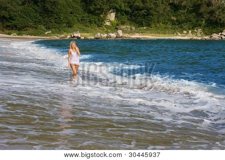 A young woman goes on sea beach.